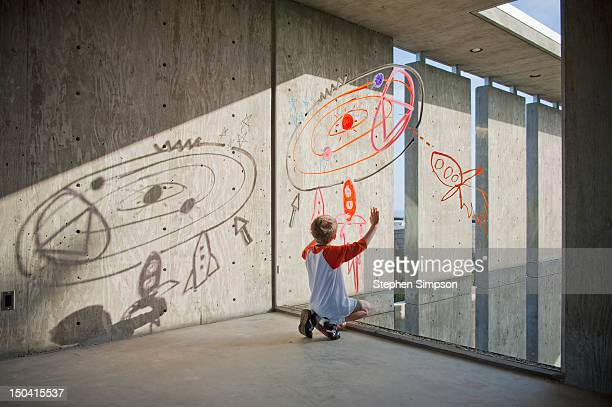 boy drawing rocket ships and planets on window