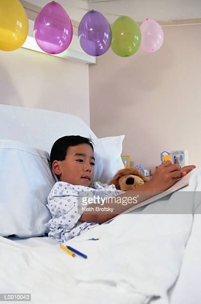 Boy Drawing with Balloons Over His Hospital Bed