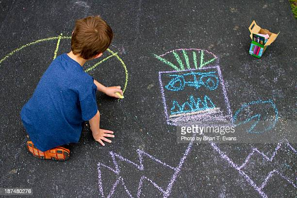 Boy drawing with chalk in his driveway