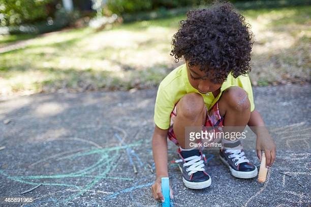 boy drawing with chalk on sidewalk - chalk drawing stock pictures, royalty-free photos & images
