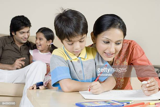 Boy drawing with his mother and a young man sitting with his daughter on a couch
