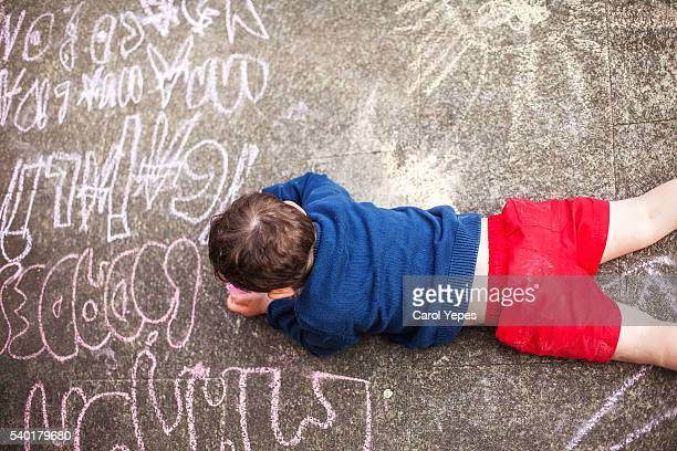 boy ( 3) drawing  with sidewalk chalk