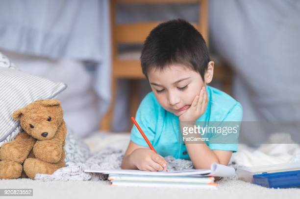 A boy draws by himself under a blanket fort in the living room