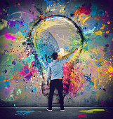Boy draws with a brush a big light bulb. Concept of innovation and creativity