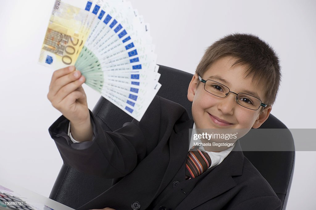 Boy dressed as a businessman holding a fan of banknotes : Stock Photo