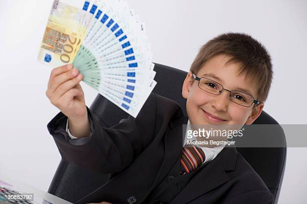 Boy dressed as a businessman holding a fan of banknotes