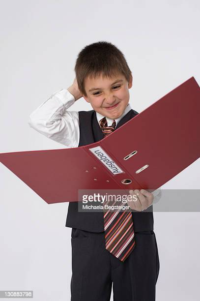 boy dressed as a businessman holding a file labeled ausgaben, german for expenditure - captions stock photos and pictures