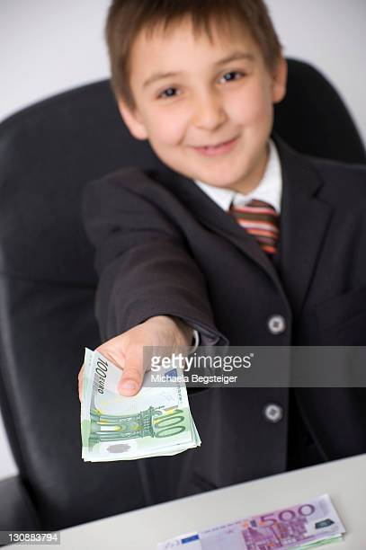 Boy dressed as a businessman offering banknotes