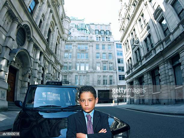 Boy Dressed as a Businessman Standing in a Road with a Taxi Behind him