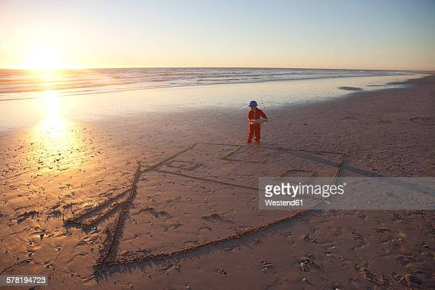 Boy dressed as a construction worker holding building plans on beach with drawn house in the sand