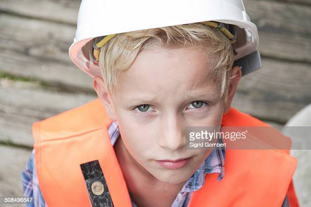 boy dressed as a construction worker with a hard hat, a safety vest and a hammer - sigrid gombert fotografías e imágenes de stock