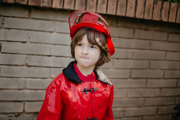 Boy dressed as a fireman in front of a brick wall