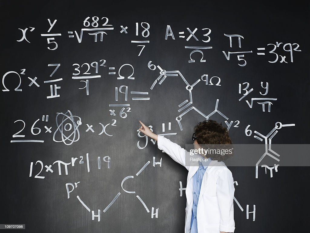 Boy dressed as a professor looking at formulas : Stock Photo