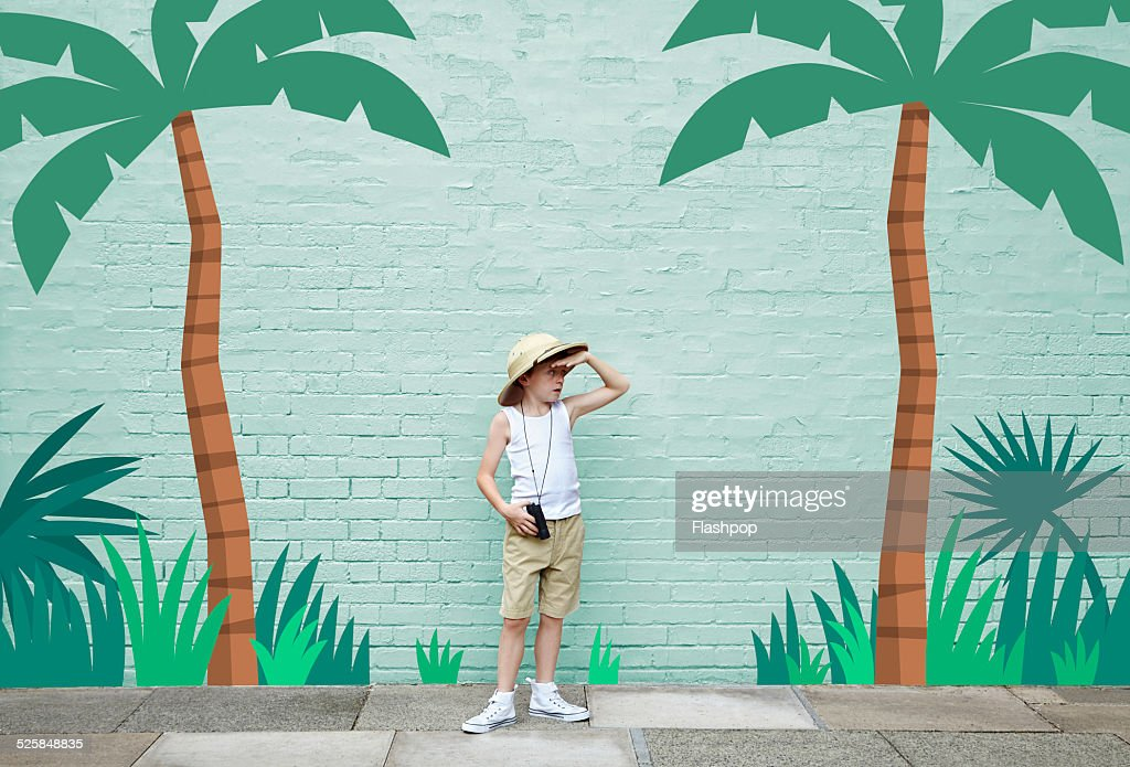 boy dressed as an adventurer with jungle scene : Stock Photo