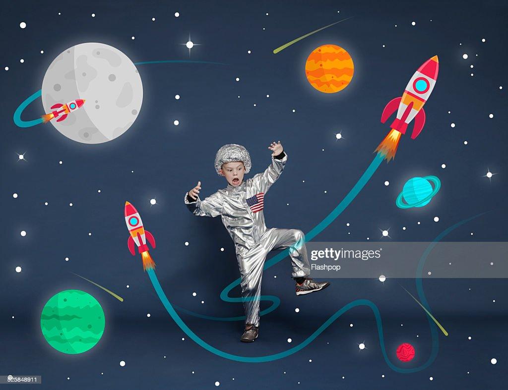 Boy dressed as an astronaut. Cartoon space scene