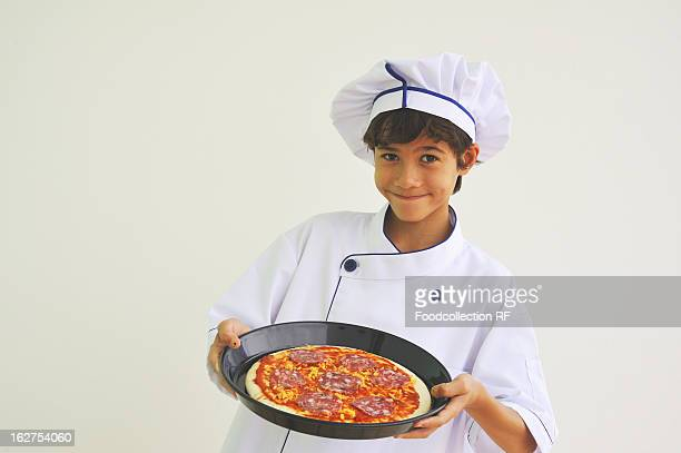 Boy dressed as chef holding pizza, smiling, portrait