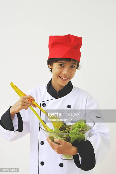 Boy dressed as chef mixing salad in bowl, smiling