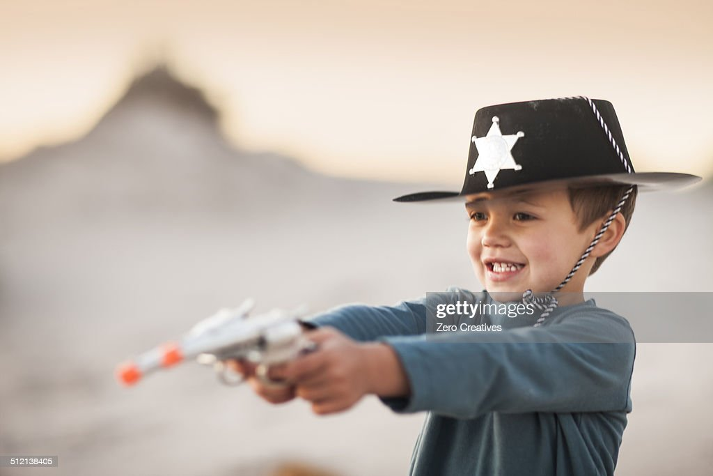 Boy dressed as cowboy sheriff holding pointing toy guns in sand dunes : Stock Photo