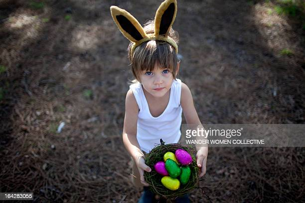 Boy dressed as Easter bunny, nest of chocolate egg