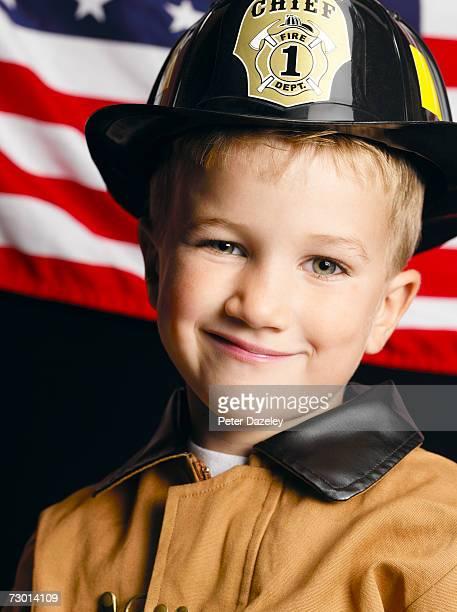 Boy (4-5) dressed as firemen, close-up, portrait