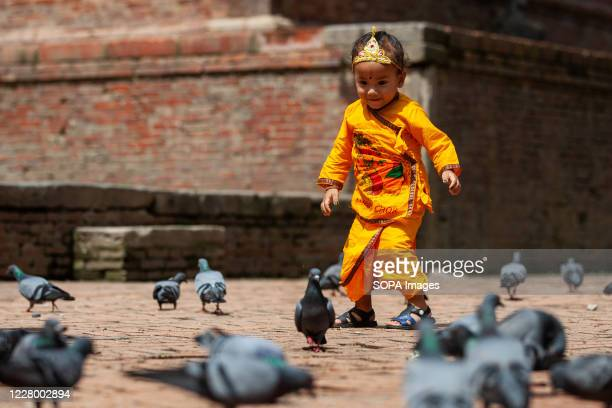 A boy dressed as Lord Krishna plays at the premises of Krishna Mandir during the Krishna Janmashtami festival which marks the birth of Hindu God Lord...