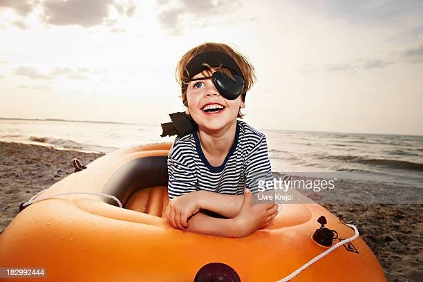 Boy (4 - 5 years) dressed as pirate on beach
