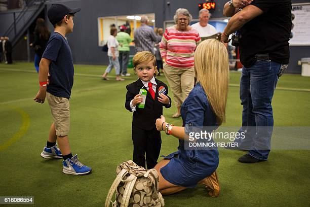 TOPSHOT A boy dressed as Republican presidential candidate Donald Trump sips juice before a rally in Newtown Pennsylvania on October 21 2016 / AFP /...