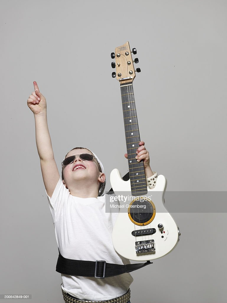 Boy (4-6) dressed as rock musician pointing upwards : Stock Photo