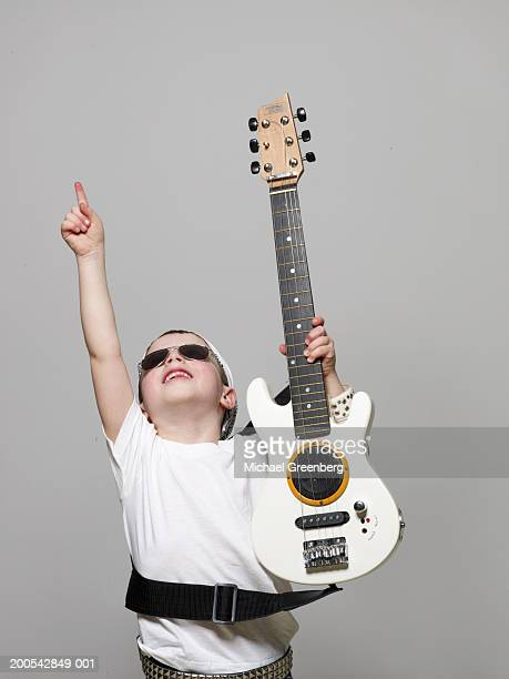 Boy (4-6) dressed as rock musician pointing upwards