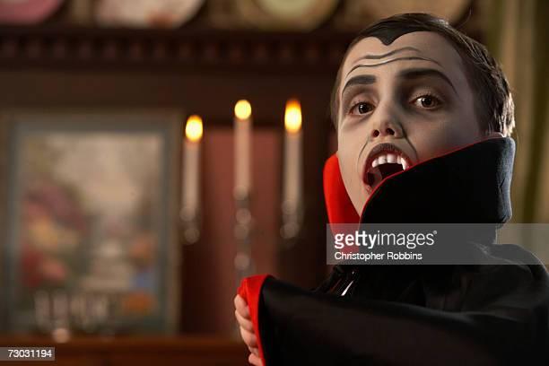 Boy (6-7) dressed as vampire posing in living room, portrait