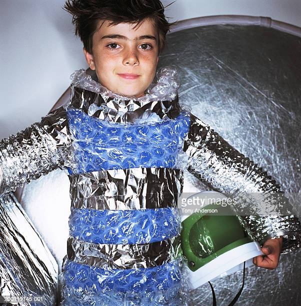 Boy (8-10) dressed in aluminum space suit, holding helmet, portrait
