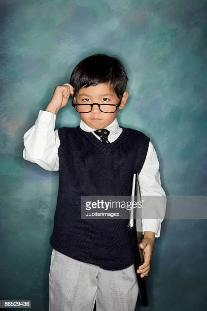 Boy dressed in business attire peering over eyeglasses