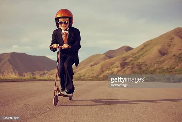 少年ビジネススーツを着てレトロなスクーターに乗って
