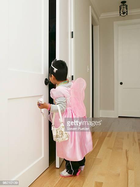 Boy dressed in girls play clothes looking in door