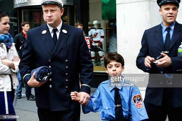 CONTENT] Boy dressed in his father's fireman's uniform shirt with two firefighters at the annual Saint Patrick's Day Parade in Midtown Manhattan New...