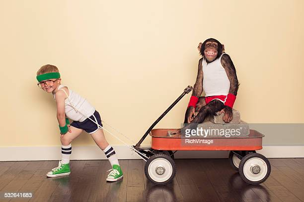 boy dressed in workout clothes pulls chimpanzee friend - toy wagon stock photos and pictures