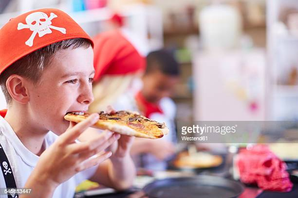 Boy dressed up as pirate eating pizza on a party