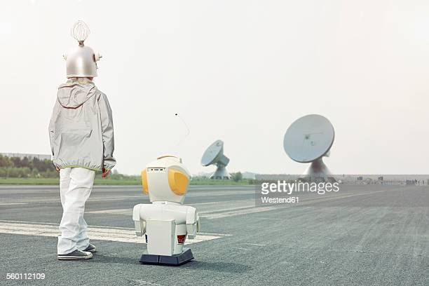 Boy dressed up as spaceman with robot
