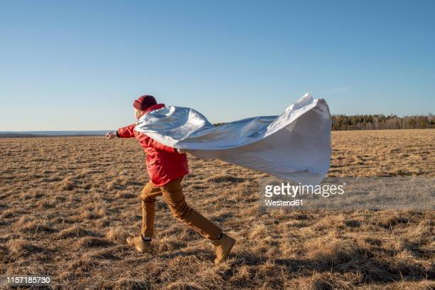 boy dressed up as superhero running in steppe landscape - cape garment stock pictures, royalty-free photos & images