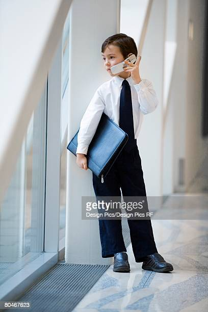 Boy dressed up like businessman and talking on cell phone