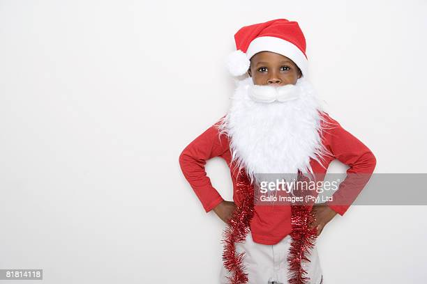 Boy dressed up like Father Christmas with a hat on his head and a fake Father Christmas Beard