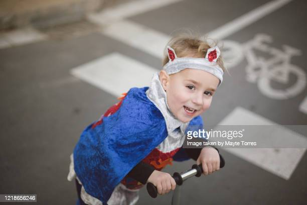 boy dressing as a prince crossing in a scooter - reality kings stock pictures, royalty-free photos & images