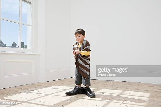 Boy dressing up in large clothes