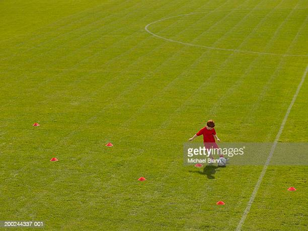 Boy (7-9) dribbling ball around practice cones on football pitch