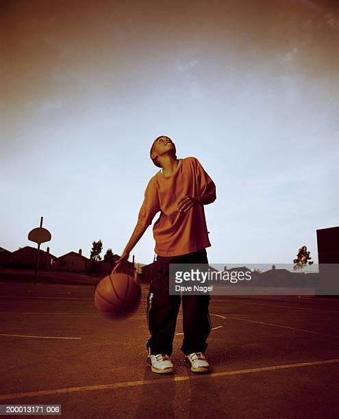 Boy (8-10) dribbling basketball and looking upward (cross-processed)