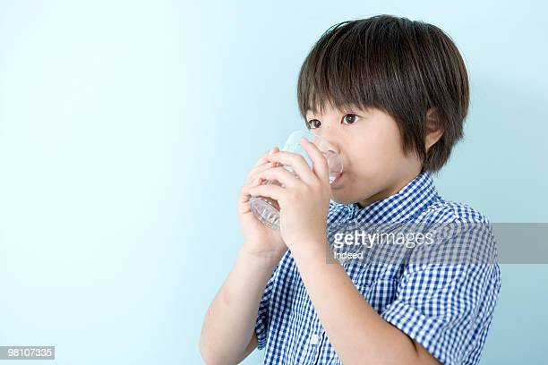 Boy (8-9) drinking a glass of water