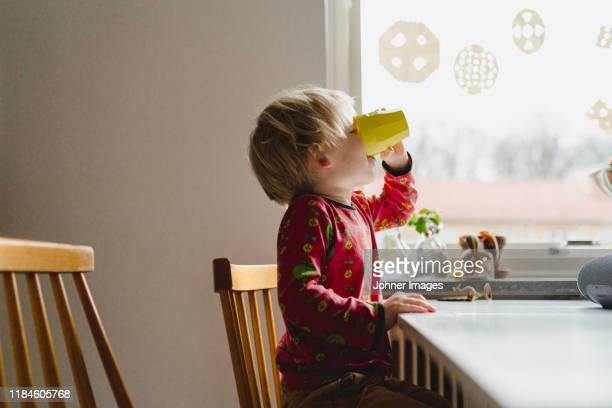 boy drinking at table - thirsty stock pictures, royalty-free photos & images