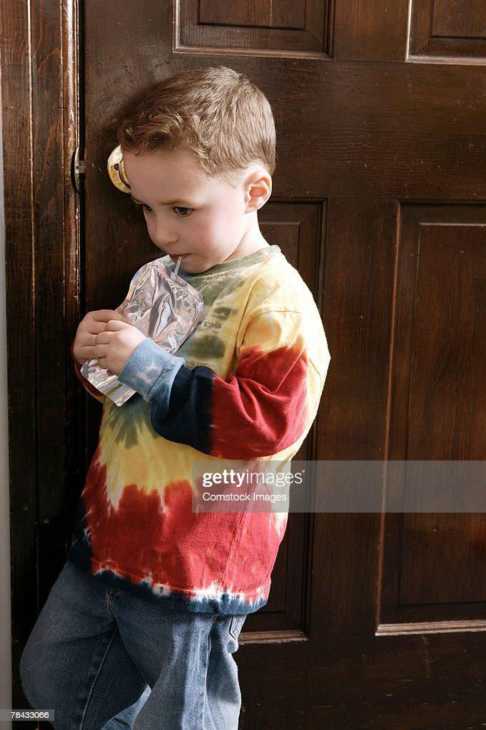 Boy drinking beverage with straw : Stockfoto