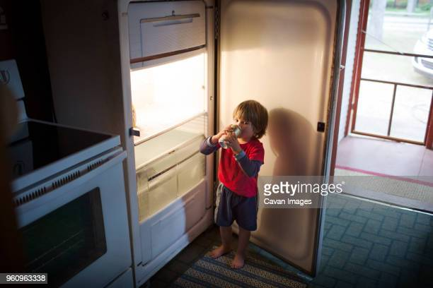 Boy drinking canned drink from fridge