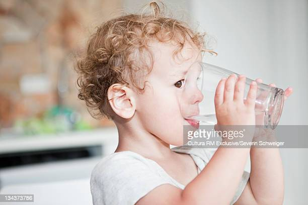Boy drinking from glass in kitchen